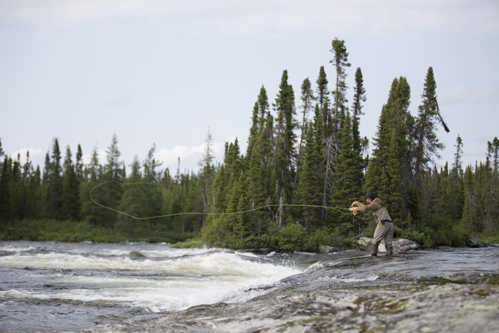 Pêcheur à la mouche sur une rivière du Québec, dans la Baie-James