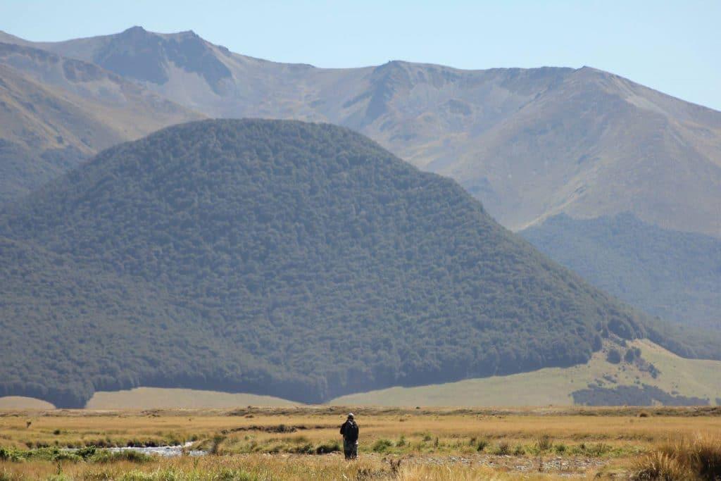 pêcheur devant une montagne en nouvelle-zélande